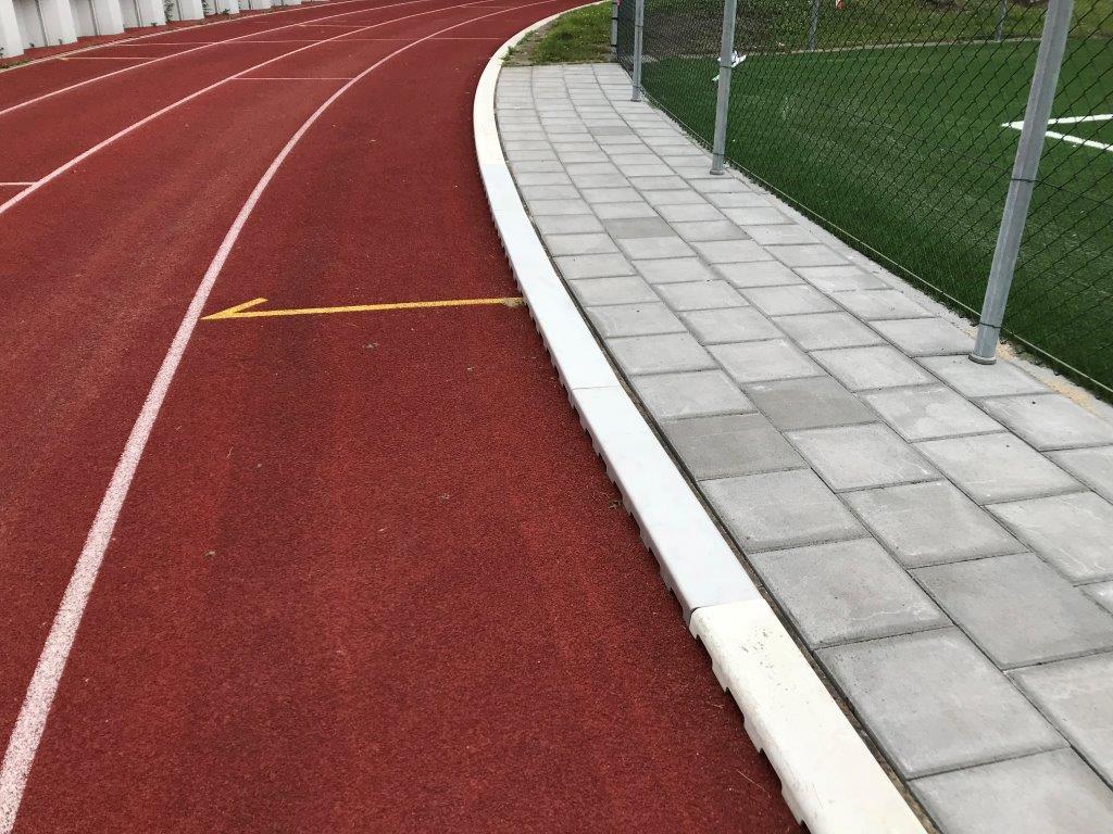 Stalen sportgoot atletiekbaan stoep groen grijs bruin